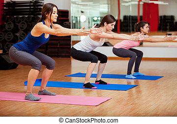 Cute women doing some squats - Three beautiful young women...