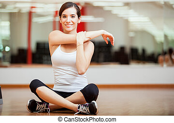 Happy girl warming up at a gym - Cute young woman stretching...