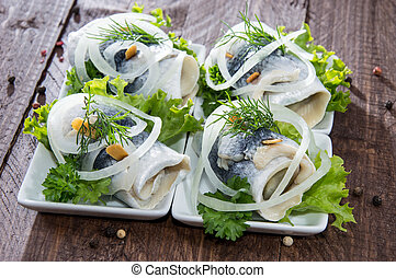 Herring Filet on small plates on wooden background
