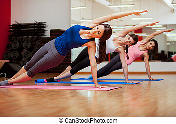 Doing a side plank for yoga class - Beautiful group of women...