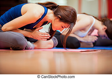 Meditation at yoga class - Group of young women relaxing and...
