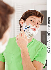 Young man shaving his beard in the bathroom