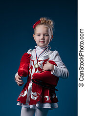 Cute little figure skater posing with bronze medal -...