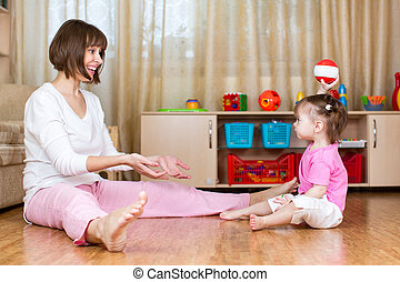 mother and kid play with toy ball indoors