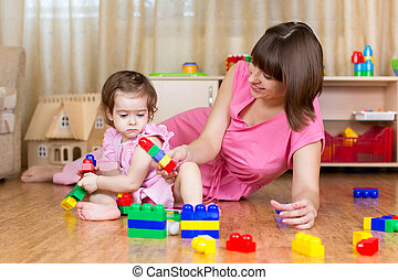 mother and her child play block toys at home