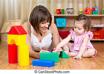 mother and her kid play with toys indoors