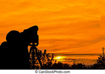 silhouette photographer at sunrise on orange clound