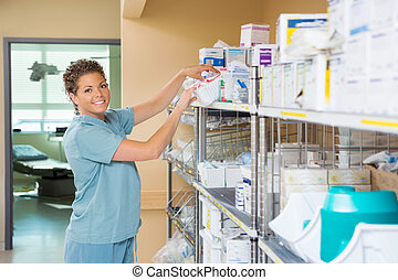 Portrait Of Nurse Working In Storage Room - Portrait of...