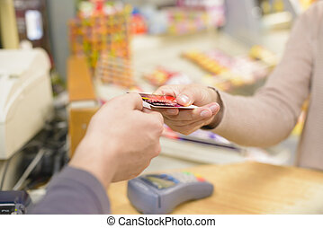Happy Shopper - Young woman paying in a shop