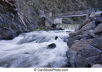 diversion dam on a mountain river flowing in deep, dark canyon