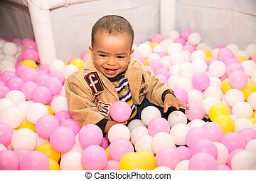 Happy black boy in colored ball on birthday on playground...