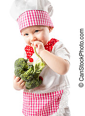 Child cook girl wearing chef hat with fresh vegetables Use...