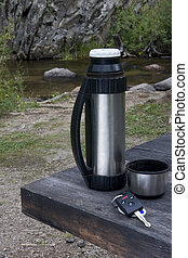 car key, steel thermos bottle and cup of tea on a roadside picnic table with scenic mountain stream in background