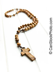 Wooden rosary beads on white wooden table