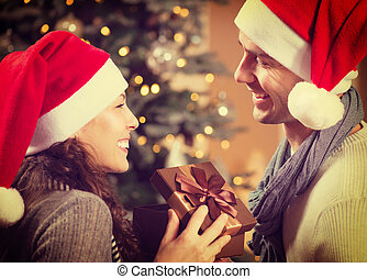 Christmas Happy Couple with Christmas Gift at Home