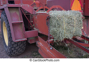 square bale of hay coming out of farm machinery - a detail...
