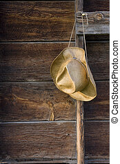 cowboy straw hat against weathered wood of old barn wall