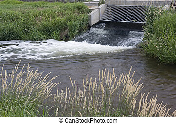 sewage flowing out from water reclamation facility -...