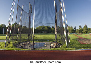 athletic field with a hammer throw cage and long jump sand...
