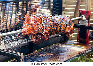 Roasted pig on the rack - Pig turning over the coals at a...