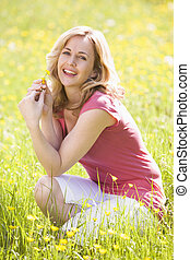 Woman outdoors holding flower smiling