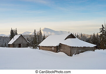 Huts in snowdrifts - Winter landscape at sunrise with...