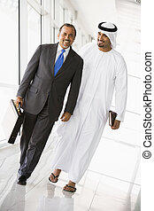 Two businessmen walking in corridor smiling (high key/selective focus)
