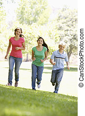 Teenagers Running Through Park
