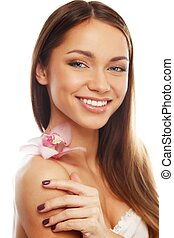 Young brunette girl with beautiful smile and orchid flower
