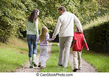 Family walking on path outdoors smiling (selective focus)