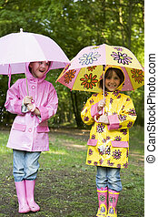 Two sisters outdoors in rain with umbrellas smiling