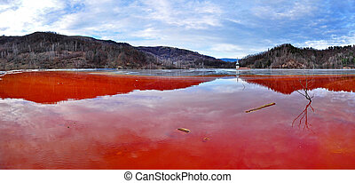 Environmental disaster. Panorama of a lake full with contaminated water from a mine in Geamana, Rosia Montana, Romania
