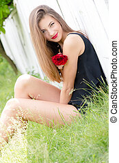 Beautiful young woman and red rose