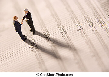 Figurines Of Two Businessmen Shaking Hands On A Financial...