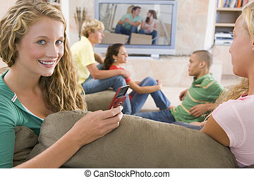 Teenagers Hanging Out In Front Of Television Using Mobile...