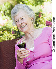Senior woman sitting outdoors on a chair with a glass of red...