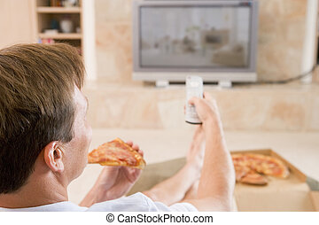 Man Enjoying Pizza While Watching TV