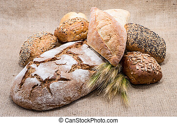 Heap of bread with wheat on textile background
