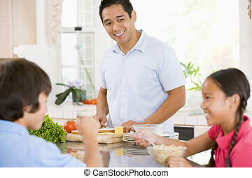 Children Having Breakfast While Dad Prepares Food