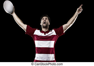 Rugby player in a red uniform celebrating. Black Background