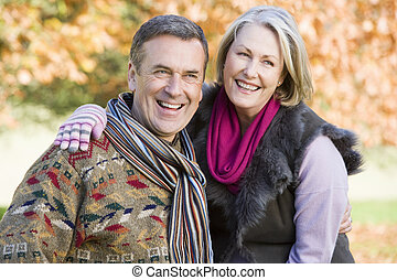Couple outdoors embracing and smiling selective focus
