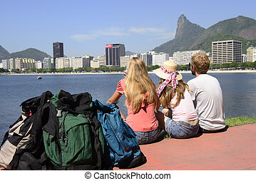Group of backpackers tourists friends sitting on the edge of...
