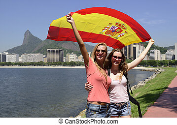 Couple of female sport fans holding a Spanish flag in Rio de...