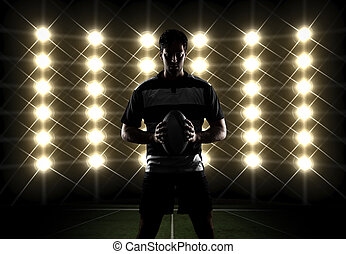 Rugby player silhouette in front of lights in a black and...
