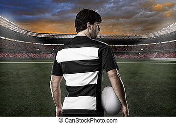 Rugby player in a black and white uniform on a stadium
