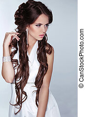 Beautiful woman with long brown hair wearing in white dress...