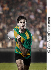 Rugby player in a green and gold uniform running on a...