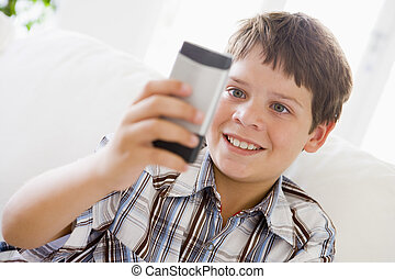 Young Boy Sitting On A Sofa Texting On A Mobile Phone
