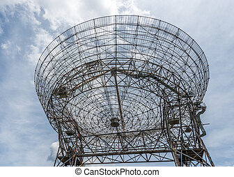 Base of a large astronomy radar with sky as background
