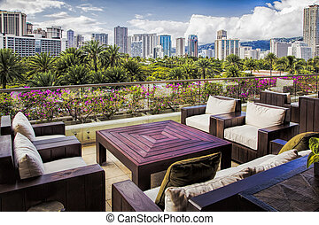 City Skyline in Honolulu - A lounge area on a deck with the...